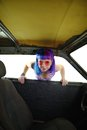 Young hipster woman looking in old rusty car isolated Royalty Free Stock Photo