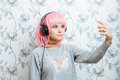 Young hipster woman in pink wig and dj headphones doing selfie against wall with vintage wallpapers pattern posing Stock Images