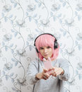 Young hipster woman in pink wig and dj headphones doing selfie against wall with vintage wallpapers pattern posing Royalty Free Stock Image