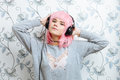 Young hipster woman in pink wig and dj headphones enjoying music against wall with vintage wallpapers pattern having fun Stock Image