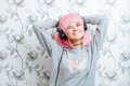 Young hipster woman in pink wig and dj headphones enjoying music against wall with vintage wallpapers pattern having fun Stock Photos