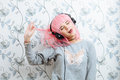 Young hipster woman in pink wig and dj headphones having fun against wall with vintage wallpapers pattern enjoying music Royalty Free Stock Photos