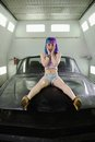 Young hipster woman sits on cowl old rusty car Royalty Free Stock Photo