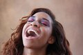 Young hispanic black woman lifts her head up laughing Royalty Free Stock Photo