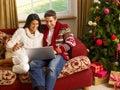 Young Hispanic couple Christmas shopping online Royalty Free Stock Photos