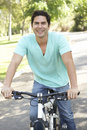 Young Hispanic Man Riding Bike In Park Stock Photography