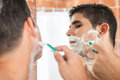 Young hispanic man shaving Royalty Free Stock Photo