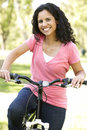 Young Hispanic Woman Cycling In Park Royalty Free Stock Photo