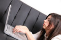 Young hispanic woman surfing on the sofa a internet with a laptop Stock Photography