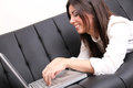 Young hispanic woman surfing on the sofa a internet with a laptop Royalty Free Stock Photo