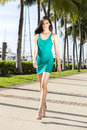 Young hispanic woman walking, outdoors. Marina with palm trees. Royalty Free Stock Photo