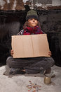 Young homeless boy on the street with a sign Royalty Free Stock Photo