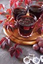 Young homemade wine, pink grape and autumn leaves Royalty Free Stock Photo