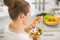 Young housewife eating fresh fruit salad rear view in modern kitchen Royalty Free Stock Photos