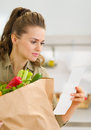 Young housewife examines check after shopping Stock Image