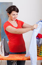 Young housewife ironing shirt beautiful at home vertical Royalty Free Stock Images