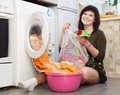 Young housewife loading the washing machine in kitchen Stock Image