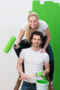 Young husband and wife painting the wall green posing with her on top of a ladder holding a roller his shoulder as they smile Stock Photos