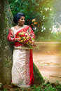 Young indian bride typical indian bridal dress women saree a woman with near a tree with bouquet of flowers in hand loction sri Stock Photography