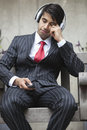 Young indian businessman with eyes closed listening music on headphones Royalty Free Stock Images