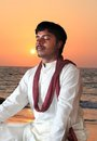 Young indian man in meditation posture at beach Royalty Free Stock Photos