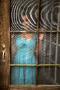 Young indian woman gazing out old screen door beautiful in an attractive blue dress looking battered Stock Image