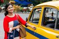 Young Indian woman opening gate of old yellow taxi Royalty Free Stock Photo