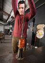 Young industrial artist pulling hot glass iron die Stock Photography