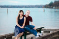 Young interracial couple sitting together on dock over lake happy Royalty Free Stock Image