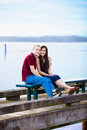 Young interracial couple sitting together on dock over lake happy Royalty Free Stock Photo