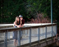 Young interracial couple standing on bridge over water happy Stock Photo