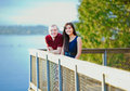 Young interracial couple standing together on wooden pier overlo happy overlooking lake Royalty Free Stock Images