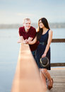 Young interracial couple standing together on wooden pier overlo happy overlooking lake Royalty Free Stock Image