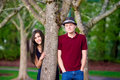 Young interracial couple standing by tree happy together Stock Image