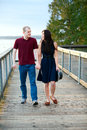 Young interracial couple walking together on wooden pier over la happy lake Royalty Free Stock Image