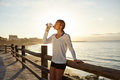 Young jogger drinking an energy drink outdoors in summertime with back lit Stock Photo