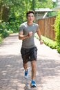 Young jogger full length portrait of a male running along the path Stock Images