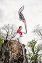 Young joyful woman is posing on the tree stump with waving scarf Royalty Free Stock Photo