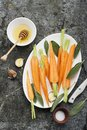 Young juicy carrots baked with honey, sage, garlic, olive oil, salt for a homely comfortable dinner on the background