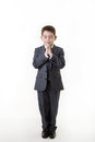 Young kid dressed up as a business person boy in office suit standing praying Royalty Free Stock Photo