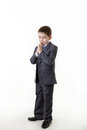 Young kid dressed up as a business person boy in office suit standing praying Royalty Free Stock Image
