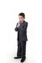 Young kid dressed up as a business person boy in office suit standing praying Royalty Free Stock Images