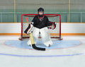 Young kid goalie in hockey net crease a protects his from a goal Stock Images