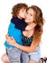 Young kid kissing his mom and looking at camera Stock Photography