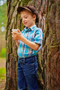 Young kid with phone boy playing games on his Royalty Free Stock Photography