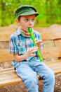 Young kid playing recorder stylish plays on green Royalty Free Stock Photography
