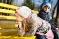 2 young kids pretty girl and boy having fun sitting & playing on a bench in the park on spring or autumn outdoors background Royalty Free Stock Photo