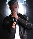 Young killer pointing his big gun at the camera closeup picture of a and smoking a cigar Stock Photography