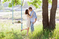 Young kissing couple under big tree with swing Royalty Free Stock Photo