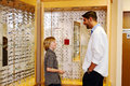 Young lad talking with optometrist checking out glasses in clinic Royalty Free Stock Images